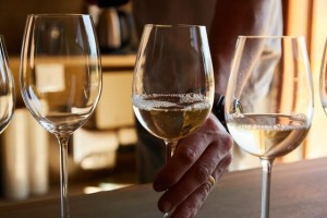 A sommelier prepares a glass of Riesling wine for tasting