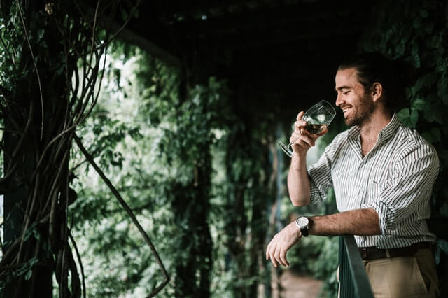 A man sniffing a glass of white wine as part of wine tasting.