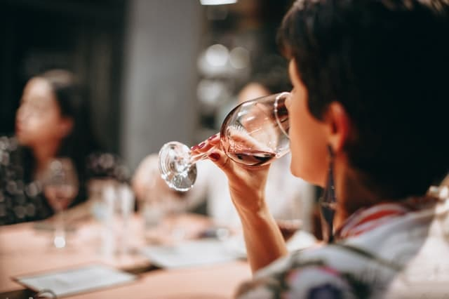 A woman sipping red wine as part of a wine tasting