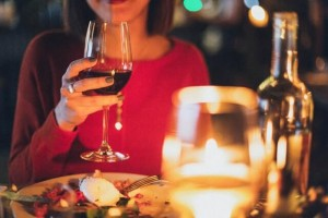 A women drinking a glass of red wine