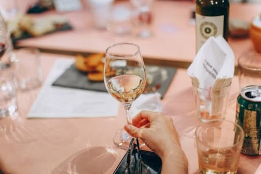 An image of a woman holding a glass of white wine